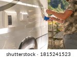 Recreational Vehicle RV Camper Van Camping Electricity Hookup Attaching to Motorhome Outlet by Caucasian Men.  - stock photo