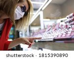 Small photo of Young woman in medical mask, sunglasses, red jacket points her finger at jewelry display. Social distance and covid 19 etiquette concept.