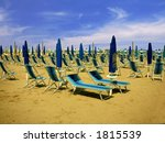 Exotic scene with parasols and chairs near the ocean - stock photo