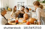 Small photo of Happy multi generational family smiling and carving jack o lantern from pumpkin while gathering around table during Halloween celebration
