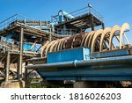 Small photo of Cement mill sand dewatering machine and machine for transferring gravel, spoil for transport belts on blue sky at an industrial cement plant.