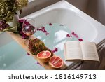 Small photo of Bath tub with flower petals, grapefruit slices, bunch of grapes, a glass of wine, opened book and hydrangea bouquet. Organic spa relaxation preparation