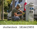 Caucasian Men in His 30s Attaching Camper Van Electric Plug to RV Park Hookup Tower. Camping Feature Theme. - stock photo