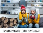 Small photo of freezing couple in warm hats and gloves looking at camera while sitting on sofa in cold kitchen