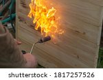 A Man Is Burning A Board With...