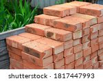 Small photo of A pile of building materials, stack of new red bricks for construction are accurately put together.