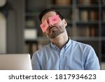 Small photo of Exhausted young Caucasian man worker have sticker pads on eyes sleeping near computer in office. Tired millennial male employee fall asleep doze off at workplace, feel overwhelmed drained at work.