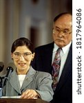 Small photo of Washington, DC.USA, August 10, 1993 Ruth Bader Ginsburg speaks to reporters in the East Room of the White House as Chief Justice William H. Rehnquist stands behind her after swearing her in