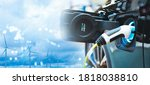 Double exposure of vehicle electric car charge battery with wind turbine and blue sky blur bokeh on panoramic background. Idea nature electric energy to generate electricity. Green energy eco concept.