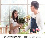 Asian beautiful woman looking at young man with smile while trimming small plant. Family couple    doing their horticultural business planting in glasshouse. Green plants interior design concept. - stock photo
