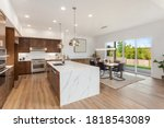 Small photo of Kitchen in new luxury home with quartz waterfall island, hardwood floors, dark wood cabinets, and stainless steel appliances. Shows view of dining area with large table and place settings.