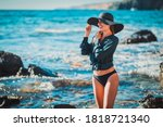 Beautiful happy lady posing in hat. Woman relaxing on sea. Summer time, amazing seascape and meditation nature concept