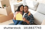 Small photo of Black millennial guy with his girlfriend hugging and holding paper house while sitting on floor of their new apartment on moving day. Relocation, tenancy, home rentals concept