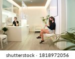 Small photo of Patient waiting at the reception of the dental, gynecological or aesthetic clinic. The patient is using her smartphone while the receptionist takes a call. Medical concept.
