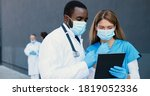 Small photo of Mixed-races couple, man and woman, doctors in medical masks talking and using tablet device. Multi ethnic male and female physicians tapping and scrolling on gadget computer. Coworking in hospital.