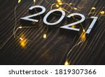Small photo of metal figures 2021 with a garland on a ninth background. new years eve