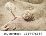 Plastic Toy Doll In The Sand....