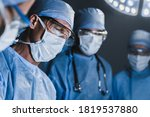 Small photo of Concentrated surgeons operating patient in operating theatre. Healthcare workers concept.