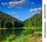 view on lake near the pine forest early in the morning on mountain background - stock photo