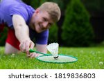 Small photo of Close up badminton player with racket in action. Young man on grass playing badminton outdoors. Sport, activity, power, confidence, energy, effort, tenacity, goal achievement concept. Focus on shuttle