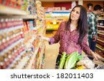 Small photo of Pretty young Latin brunette picking up some food at the grocery store