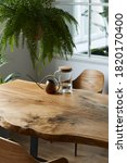 Small photo of Stylish and cozy compositon of craft oak wooden table with chairs, watering can, glassy jug and modern floor in beautiful interior of design home. Template.