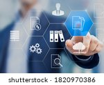 Small photo of Document Management System (DMS) used to store, search and manage review process and users for corporate files and information in enterprise. Concept with business manager pointing to icons.