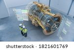 Small photo of Industry 4.0 Two Engineers Standing and Talking in Factory Workshop with Augmented Reality 3D Model Concept of Giant Turbine Engine. Graphics Visualization. High Angle Shot. VFX Special Visual Effects