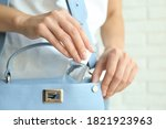 Small photo of Woman putting hand sanitizer in purse on light background, closeup. Personal hygiene during COVID-19 pandemic