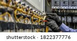 Small photo of Electrical engineer using measuring equipment to checking electric current voltage at circuit breaker and cable wiring system for maintenance in main power distribution board.