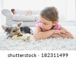 little girl lying on rug with... | Shutterstock . vector #182311499