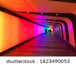 Small photo of London / UK - September 2020: Colourful pedestrian tunnel at King's Cross Station in London. You can see shapes of people far away at the other end of the tunnel.