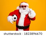 Small photo of Portrait of his he nice attractive cheerful cheery Santa holding in hands ball celebrating having fun win winner luck attainment isolated over bright vivid shine vibrant yellow color background
