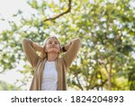 Small photo of Portrait photo of happy senior Caucasian woman relaxing and breathing fresh air with sunlight in outdoors park. Elderly woman enjoying a day in the park on summer. Healthcare lifestyle and wellness