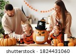 Small photo of Cheerful family makes jack o lantern in medical masks out of a pumpkin and decorates house in cozy kitchen during Halloween celebration at home during the covid19 coronavirus pandemic