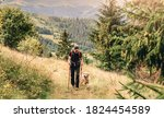 Hiker With Dog Walking Along...