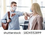 Small photo of Say hello and greet, social distance and return to work after quarantine. Millennial man and woman in protective masks are touched by elbows in interior of office during COVID-19 epidemic, free space