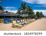 Small photo of PLACENCIA, STANN CREEK DISTRICT / BELIZE - JUNE 2018: Colourful wooden sun beds outside the beachfront Tipsy Tuna bar on Placencia Beach, Belize, September 2018.