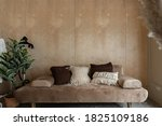 Small photo of Stylish living corner with velvet tan color sofa setting with soft pillows with plywood wall on the background / cozy interior design / modern interior