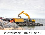 Small photo of The excavator is loading excavation to dump truck. Modern hydraulic excavators come in a wide variety of sizes. The smaller ones are called mini or compact excavators.