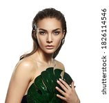 Small photo of A beautiful young woman in the studio on a white background with wet skin and wet hair holds a large green tropical leaf in her hands and covers a part of her body. Natural cosmetics, natural beauty.