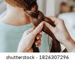 Two Girls Braid Their Hair At...