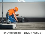 Caucasian Residential Building Lightning Protection System Installer in His 40s Finishing His Work on the Building Roof.  - stock photo