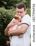Small photo of Portrait of young happy man holding his newborn cute babe dressed in white clothing. father embracing tenderly his adorable newborn child and smiling Outdoors. father's day