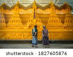 Small photo of Sakonnakhon, Thailand - Sep 22, 2020: A monk is waxing on wax castle to prepare for the wax castle Parade. Where each temple is made after each temple To attend the wax castle parade .