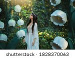Small photo of beautiful elf girl. long hair walks in fantasy spring forest. Huge flowers lilies of the valley, green trees, art creative decorations. White long medieval dress. Woman inhales smells scent summer