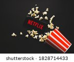 Small photo of Ufa, Russia - October 7, 2020: Table with popcorn and Netflix logo. Netflix is a global provider of streaming movies and TV series.