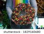 Small photo of Person holding beautiful and colourful hand made Christmas wreath, green spruce branches decorated with pine cones and other decorations. Christmas chaplet in hands.