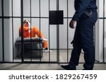Small photo of A prison guard makes a tour of the cells in a high-security prison. The cells are occupied by criminals in red robes