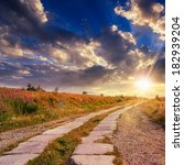 road of concrete slabs through the field turns uphill to the sky at sunset - stock photo